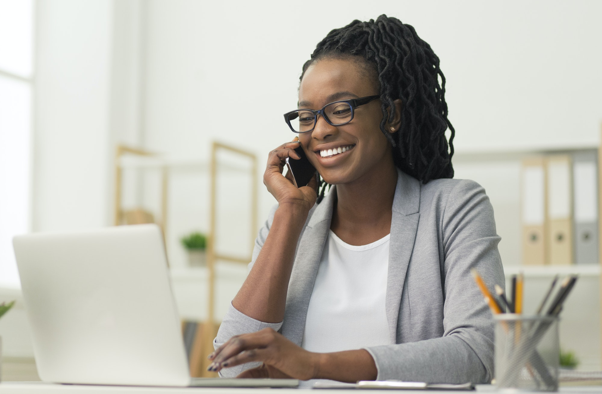 Black Young Lady Having Phone Conversation Sitting At Workplace